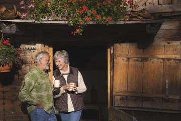 Österreich, Karwendel, älteres Paar lehnt an Blockhaus, hält Becher