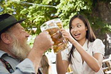 Deutschland, Bayern, Oberbayern, Bayerischer Mann und asiatische Frau im Biergarten Anhebung stein Gläser, Porträt