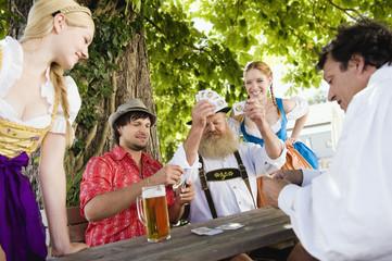 Deutschland, Bayern, Oberbayern, Menschen spielen Karten im Biergarten