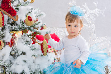 Little girl  is decorating christmas tree