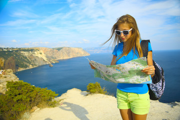 girl with a travel map for mountain coast