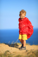 little boy dressed as superhero on the coast