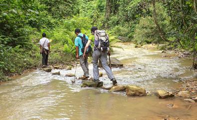 trekkers crossing a river