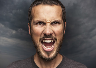 portrait of a young beautiful man screaming