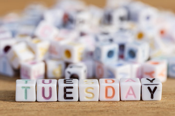 Tuesday written in letter beads on wood background