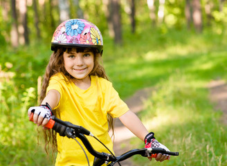 little girl on bike in forest looking at camera and smiling