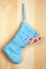 Blue christmas boot with gifts on background wooden wall