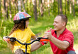 father praises his daughter, who learned to ride a bike