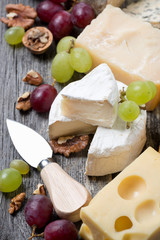 assortment of cheeses, grapes and walnuts on a wooden background