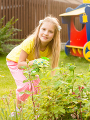 Girl sprays plants in the garden