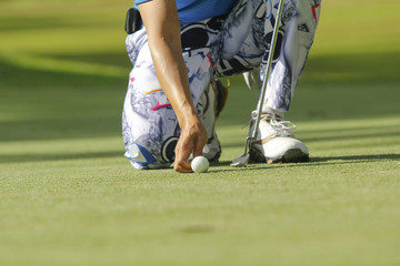 Golf player squatting to put down ball at green