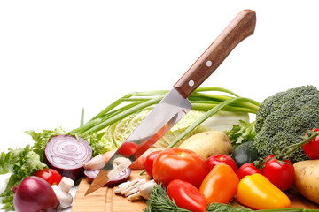 Fresh vegetables with knife on white background