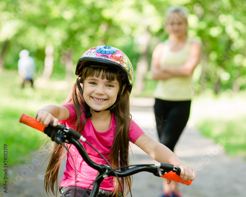 mom and daughter ride bikes in the forest - 74033319
