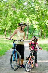 Happy mother talking with her daughter riding a mountain bike