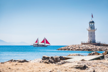 Lighthouse and tourist yacht by the sea