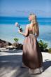 The beautiful woman in a long dress near the sea
