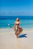 woman with a rose runs on the edge of sea on beach - 74035573