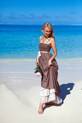 The young beautiful woman with a rose near the sea, tropics