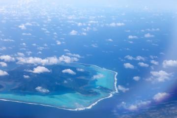 Polynesia. The atoll in ocean through clouds. Aerial view...