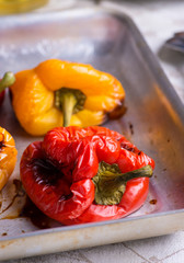 Fresh roasted red and yellow peppers on metal tray