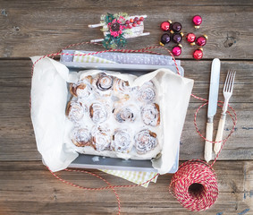 Cinnamon buns with cream-cheese icing in a baking dish with Chri