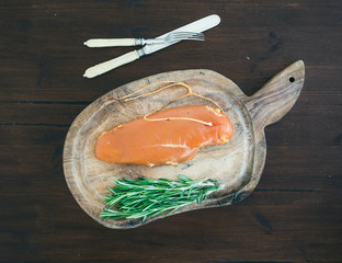 Chicken carpaccio and rosemary on a rustic wooden board over a d