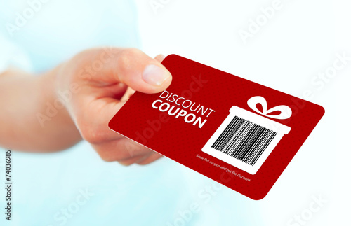 red christmas coupon holded by hand over white - 74036985