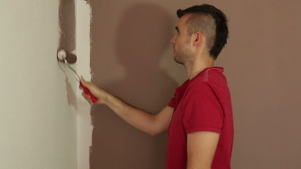 Man with a paint roller painting white wall using brown color.