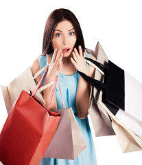 Portrait of surprised young woman carrying shopping bags