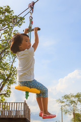 An Asian small girl plays the rope flying