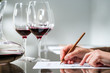 Female hand taking notes at red wine tasting. - 74040521
