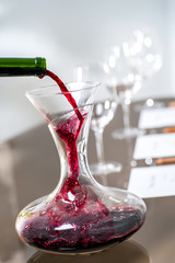 Red wine pouring into decanter at wine tasting.