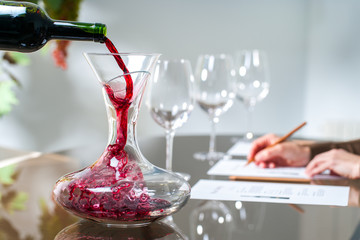 Sommelier pouring wine into decanter.