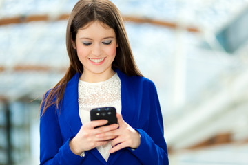 Smiling businesswoman sending a sms