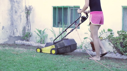 Woman with a lawn mower mowing the grass.