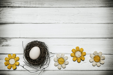 Egg in nest with flowers around on wooden background