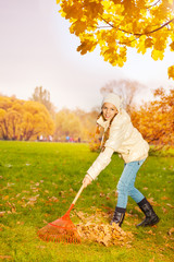 Positive smiling girl with rake cleaning grass