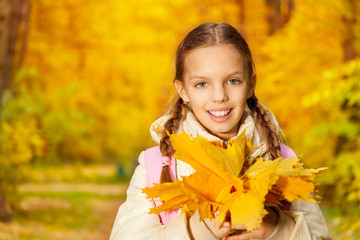 Portrait of girl with autumn yellow leaves bunch