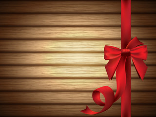 Red Silky Bow with Ribbon over Wooden Background