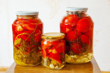 three glass jars with marinated tomatoes homemade