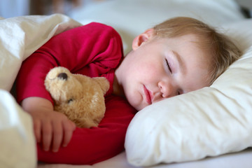 Toddler girl sleeping in bed with teddy bear