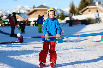 Happy school boy enjoying winter ski vacation