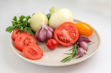 Tomatoes, garlic, onions and greens on a plate