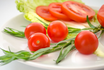 Fresh tomatoes, tarragon, onions on a plate