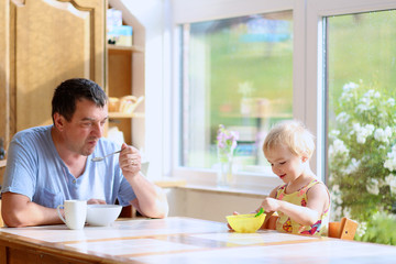 Father and daughter having breakfast in the kitchen