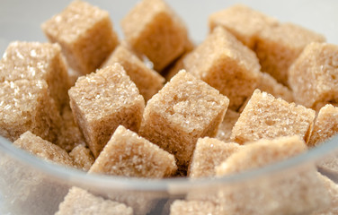 Brown cubes of cane sugar in the glass cup
