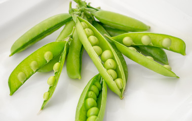 Pods of fresh green peas on a plate