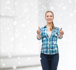 smiling girl showing thumbs up over white room