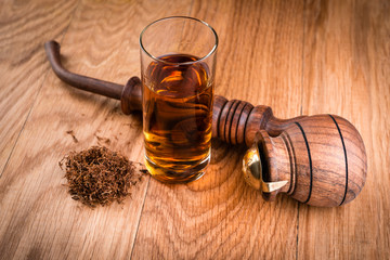 cognac or brandy and smoking pipe on  wooden table