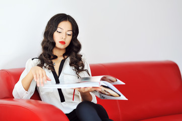 Woman sitting on a sofa and reading magazine